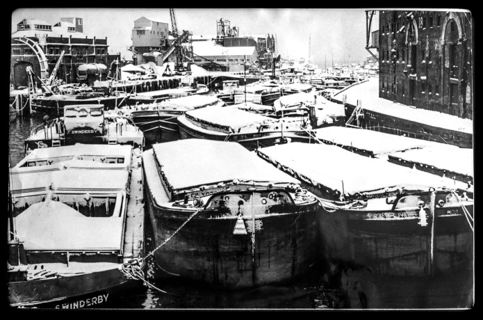 January Riverfront Snowscape. Barges pack the river under a mantle of white
